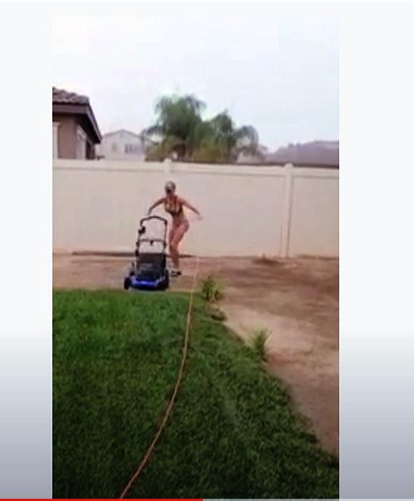 Woman in bikini use electric lawn mower to cut grass
